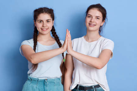 Two young brunette females showing high five, posing isolated over blue background, smiling girls wearing white t shirts, women looking at camera with positive emotions.