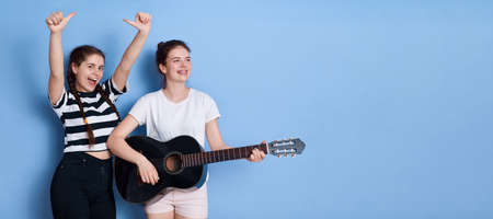 Two young girls with guitar play and sings, look happy, dancing, lady with pigtails raising hands up and showing thumbs up, posing in casual shirts against blue wall. 免版税图像