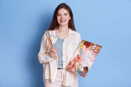 Attractive young Caucasian female artist with painting accessories, holding brushes, mixing colors on palette, lady wearing white shirt and trousers. 免版税图像