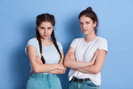 Two amazing ladies standing with angry expressions, dislike each other, being in bad mood, wear casual white t-shirts, posing isolated isolated over blue background.