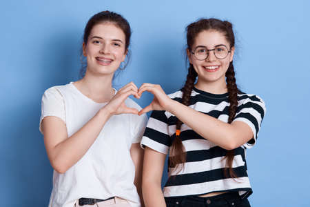 Two young smiling females in casual clothing making heart using their hands, looking at camera with toothy smiles, wearing white and striped t shirts, posing isolated over blue background.