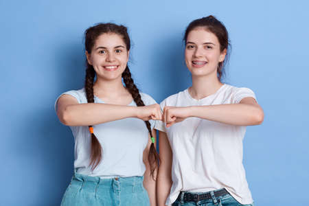 European young women give fist bump to each other, showing they friendly team, have positive expressions, wearing casual clothing, females wearing white t shirts. 免版税图像