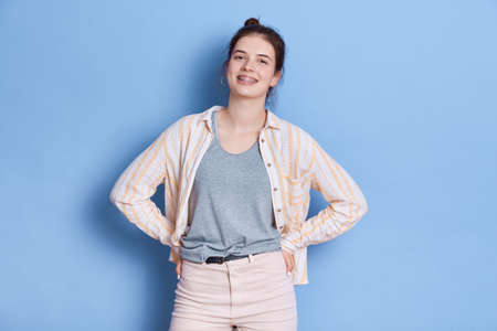 Cheerful woman keeps hand on hips, being in good mood, wears white shirt and trousers, has knot, posing isolated over blue background, looks at camera with toothy smile. 免版税图像