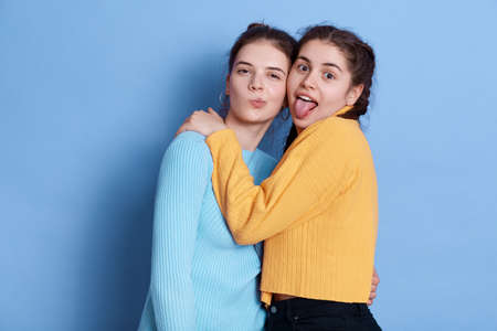 Two positive Caucasian young girlfriends hugging and having fun while posing isolated over blue background, ladies making grimace and showing tongue, wearing casual attires.