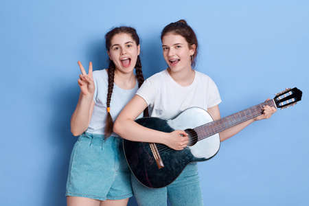 Happy women friends with guitar and showing v sign, keeping mouths opened, wearing white t shirt and jeans shorts, posing isolated over blue background, happy females, singing songs. 免版税图像