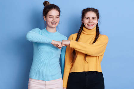 Two caucasian women fist bumping against blue wall, two friends greeting, females wearing casual shirts, have dark hair, expressing happiness and positive emotions. 免版税图像