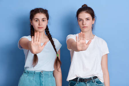 Portrait of serious, unhappy, confident brunette women gesturing two palms front, showing stop symbols, looking at camera, standing against blue background, wearing casual attires.