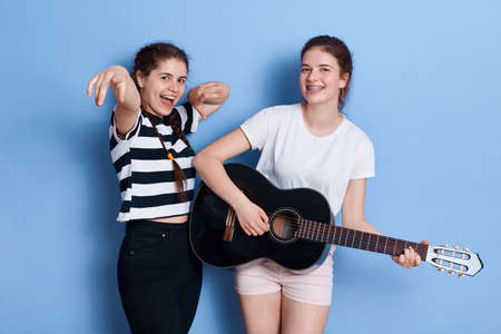 Two brunette young funny girls dance singing and playing acoustic guitar while standing isolated over blue background, sisters having fun leisure at home, wearing casual attires.