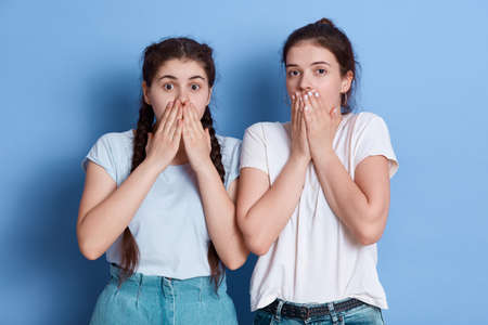 Two shocked women dress whit casual t shirts posing against blue wall covering their mouths, standing with shocked facial expressions, brunette ladies look astonished.