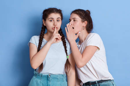 Two attractive dark haired young women posing against blue wall, lady with knot whispers to her mate shocking news, female with pigtails looks at camera with finger near lips, showing shh signs.