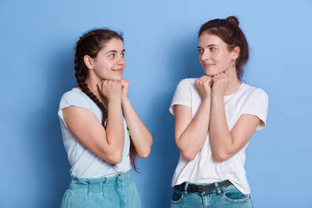 Two shy women friends european girls in casual clothes posing isolated over blue wall, ladies looking at each other keeping fists under chin.