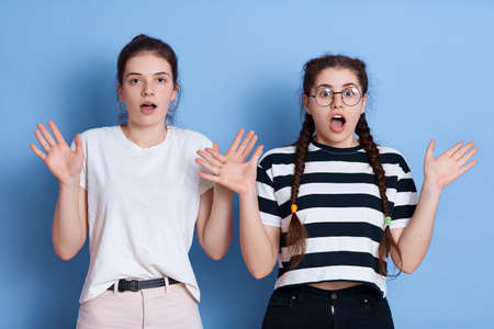 European dark haired girls posing with hands up, widely opened mouth, having shocked facial expressions, express fear, wearing casual t shirts, posing against blue wall. 免版税图像
