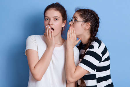 Two young beautiful dark haired girls with astonished expressions, lady with pigtails tells secret to he friend, females wearing casual t shirts, covering mouth with hands while gossiping. 免版税图像