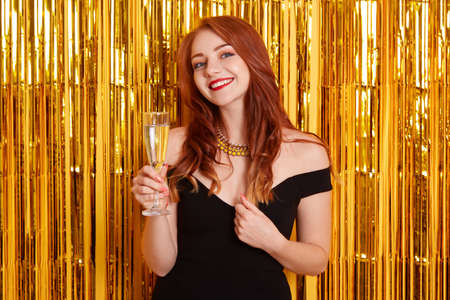 Woman with charming smile celebrating birthday in restaurant, holding glass of wine, looks at camera, wearing elegant black dress, posing against yellow wall with golden tinsel. Stock fotó