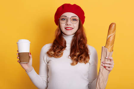 Portrait of girl with long red hair wearing beret, white shirt and glasses, looks at camera and smiles, holding bread in paper bag and take away coffee, model posing against yellow wall.