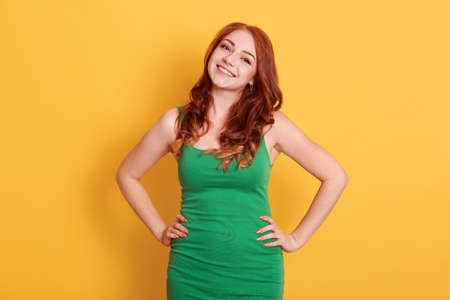 Smiling elegant red hair woman in green dress posing with hands on hip and looking directly at camera, standing isolated over yellow background, female with happy expression.