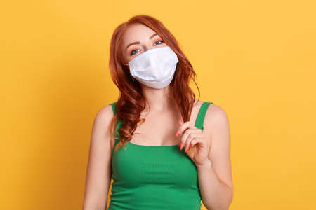 Close up shot of young woman with wavy hair, wears green t shit and medical disposable mask, cares about her health, protects in dangerous situation, standing against yellow wall.