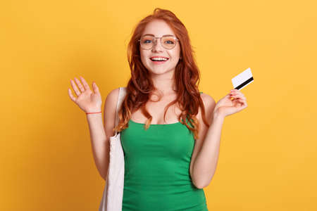 Young Caucasian woman with shopping bag and blank credit card posing with spreading hands and excited facial expression, wearing green t shirt, has red wavy hair.