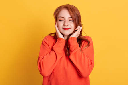 Red haired woman plugging ears with fingers and closing her eyes, not wanting to listen hard loud music, ignoring noise or avoiding loud sounds, wearing casual sweater.
