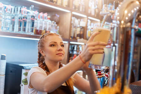 Beautiful red haired waiter tapping beer into glass, looks concentrated at tap, wearing white casual t shirt, showcase with alcohol on background, barman i cafe working.