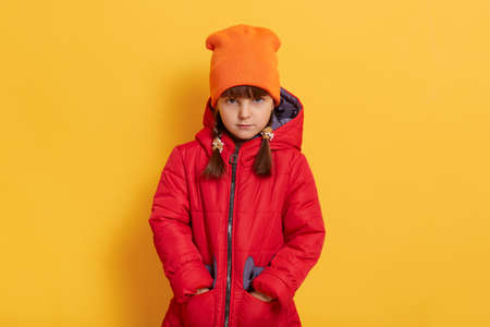 Sad offended little girl wearing orange cap and red jacket standing against yellow wall and looks at camera with upset facial expression, keeps hands in pockets.