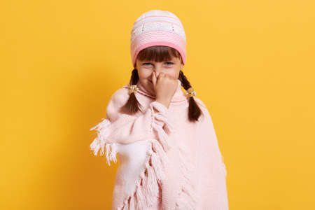 Caucasian girl feeling bed smell, looking smiling at camera and closing nose with finger, little girl wearing rose cap and poncho, standing isolated over yellow background.