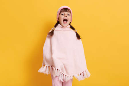 Young little girl dresses poncho and cap, standing against yellow wall and yelling happily, looks at camera with widely opened mouth, female child with pigtails
