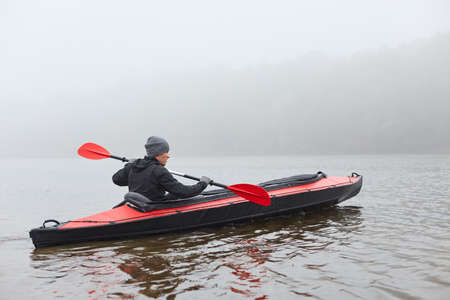Kayaker paddling in water, holding oar in hands, sportsman in canoe, water sport, guy in jacket rowing boat in cold autumn foggy morning, active extreme rest. Stock Photo