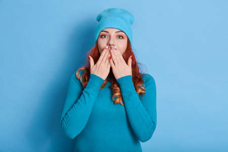 Stunned red haired woman with wavy hair, covers both hands on mouth, afraids of something, looks astonished, dressed in casual shirt, isolated over blue background, stands speechless indoor.