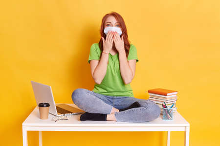 Photo of smart intelligent girl sits on table, preparing for exam or test, wears medical mask, green casual t shirt and jeans, works with lap top, isolated on yellow background, cover mouth with palms Imagens