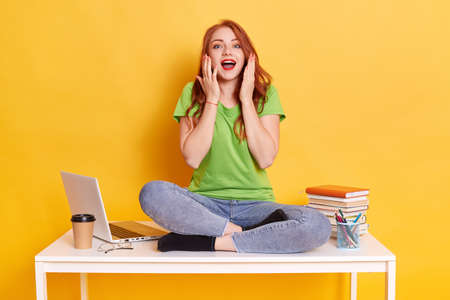 Excited Caucasian girl freelancer sitting on desk isolated on yellow background. Achievement career. Education in university or college, female with red hair posing with opened mouth, raising palms.