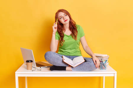 Pensive red haired female student sitting on desk with crossed legs, looking aside with thoughtful facial expression, keeping pen near her temple, wearing casually, doing school tasks. 免版税图像