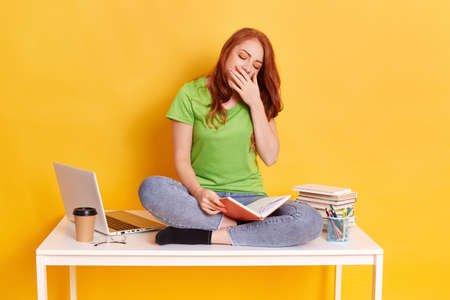 Adorable red haired tired sleepy woman sitting on her desk with books and computer, keeps eyes closed, covering her mouth while yawning, spending long hours studying against yellow wall.