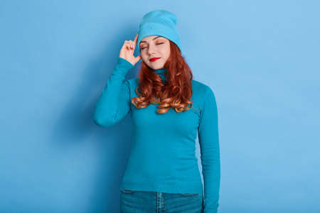 Red haired young adult woman calm face and keeps index fingers on temple, tries to remember something poses indoor alone, red haired lady in sweater and cap.