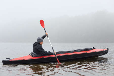 Profile of man floating on lake in kayak, looking concentrated on his way, rowing boat in cold cloudy day, water sport, guy in black jacket padding, pastime in active way.
