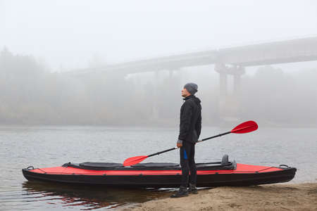 Pensive male wearing black clothing and standing with oar in hands near his kayak on bank of river, looks at water, posing with thoughtful expression with bridge on background. 免版税图像