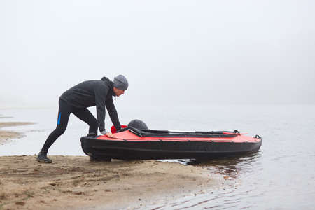 Man pulling canoe into water, wearing black clothing, posing on bank of river, handsome sports man doing water sport in foggy autumn day, canoeing in cloudy morning.