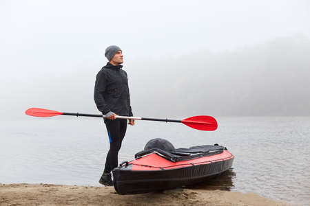 Young man athlete carrying canoe oar, looking into distance, wearing black trousers, jacket and gray cap, holding red oar in hand, looking into distance with dreamily expression.
