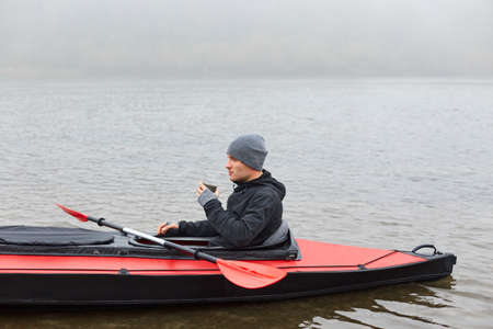 Man paddles red and black kayak and sitting with paddle, holds mug with hot coffee or tea on river or lake in fall season. Autumn kayaking, water extreme sport. 版權商用圖片 - 158010094
