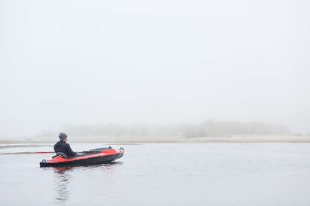 Rear view of handsome man sitting in canoe and looking in distance, guy wearing black jacket and cap, foggy autumn morning, sportsman padding in lake.