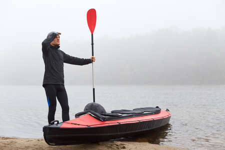 Full length shot of handsome young man wearing black clothing and cap, holding oar in hand and looking into distance with palm near forehead, sports man planning his way canoeing.