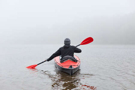 Back view of man floating on lake in kayak at cold foggy day, holding oar in hands, wearing black jacket, spending his leisure time doing water sport. 免版税图像