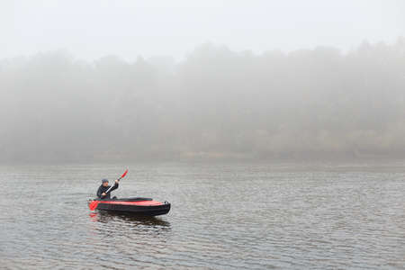 Simple dugout canoe on lake, young athlete rowing boat in autumn cloudy day, guy in black jacket canoeing, spending leisure time in active way, doing water sport. 免版税图像