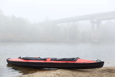Red and black canoe on lake coast, bridge across river on background, foggy cloudy day, water sport, oar on kayak.