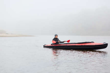 Young Adult Man rowing boat on lake, holding oar in hands, looking directly at camera, wearing casual warm clothing, posing in middle of river, spends cloudy autumn day in active way.