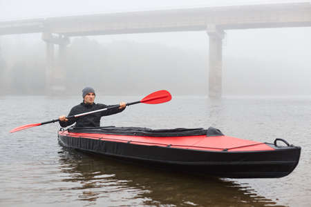 Front view of man paddles in kayaks on calm lake or river near bridge in cloudy autumn day, guy looks straight ahead, holding oar in hands and rowing, wearing black jacket and cap.