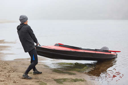 Travel on river in kayak on foggy day, back view of sports man getting kayak out from water, male like water sport, finishing padding in foggy autumn morning.