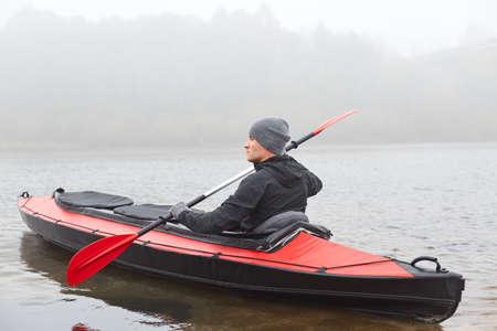 Side view of man kayaking on river in cold autumn cloudy day, kayaking, sports and recreation, male wearing black jacket rowing boat, water sport, leisure time in open fresh air.