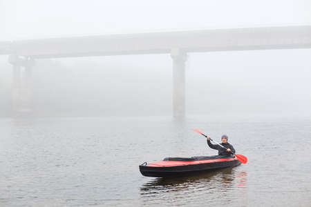 Man canoeing in traditional wooden kayak on large lake at cold cloudy day, fog over water, handsome guy wearing black jacket and gray cap, kayaking alone in lake with bridge on backround.