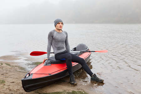 Young man sitting on his canoe after kayaking, sportsman having rest, male padding, wearing sports clothing and cap looking directly ar camera with confident look. 免版税图像